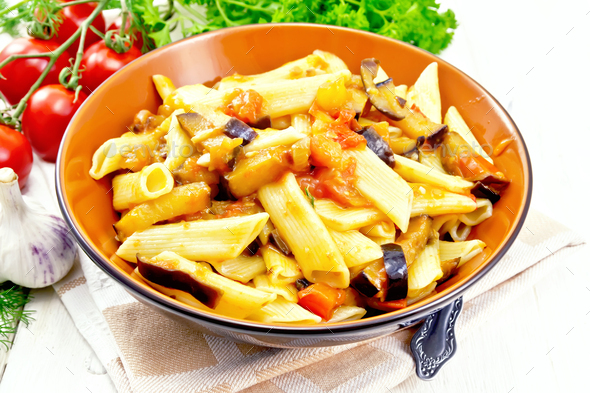 Pasta penne with eggplant and tomatoes on board - Stock Photo - Images