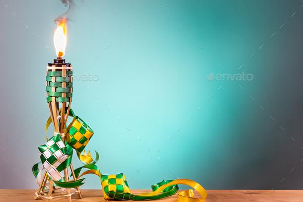 Traditional Malay torch and decorative ketupat lit up during Hari Raya Aidilfitri celebration - Stock Photo - Images