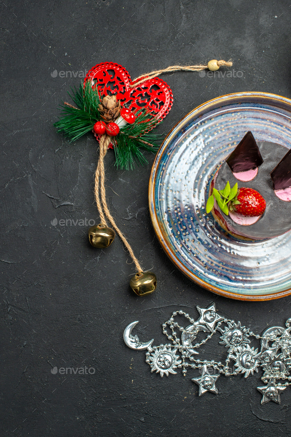 top view delicious cheesecake with strawberry and chocolate on oval silver plate xmas pendants on - Stock Photo - Images