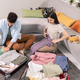 Contemporary young couple in casualwear sitting on the floor by large couch and packing clothes - PhotoDune Item for Sale
