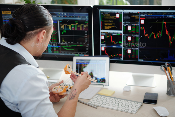 Broker eating at office desk - Stock Photo - Images