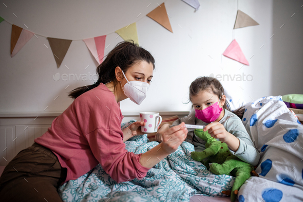 Mother looking after sick small daughter in bed at home, coronavirus concept - Stock Photo - Images