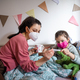 Mother looking after sick small daughter in bed at home, coronavirus concept - PhotoDune Item for Sale