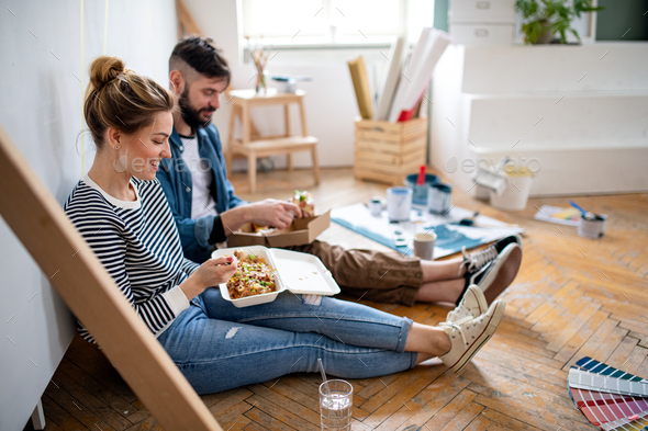 Couple eating lunch indoors at home, relocation, diy and food delivery concept - Stock Photo - Images