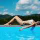 Young woman sunbathing by swimming pool outdoors in backyard garden - PhotoDune Item for Sale