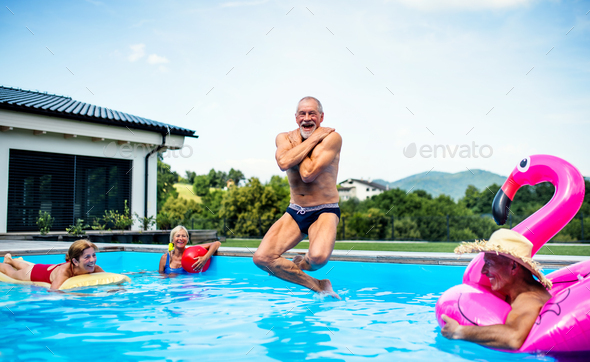 Group of cheerful seniors in swimming pool outdoors in backyard, jumping - Stock Photo - Images