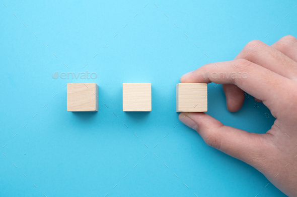 Hand holding a row of three blank wooden cubes - Stock Photo - Images