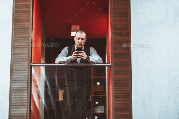 A businessman on an office balcony - Stock Photo - Images