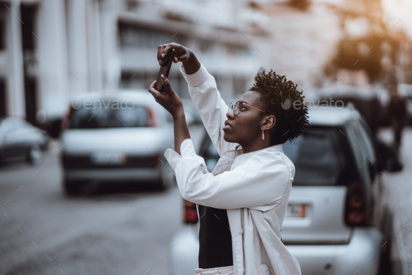 Black girl is taking pics outdoors - Stock Photo - Images