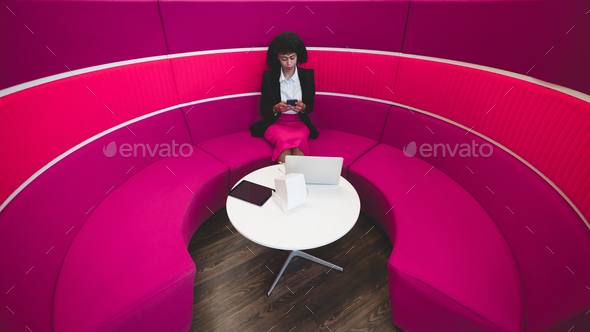 Businesswoman on a pink bent sofa - Stock Photo - Images