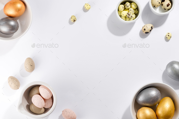Many multi-colored Easter eggs in bowls of different sizes on a white background - Stock Photo - Images