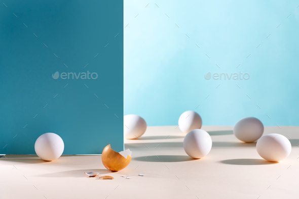 Easter background. White eggs with golden shell on a blue background - Stock Photo - Images