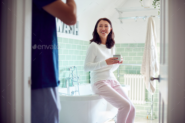 Mature Asian Couple Wearing Pyjamas Sitting In Bathroom Enjoying Morning Hot Drinks Together - Stock Photo - Images