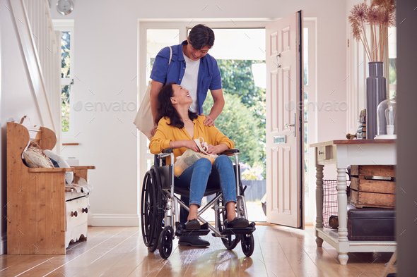 Asian Man Pushing Wife In Wheelchair At Home Back From Shopping Trip With Bag - Stock Photo - Images