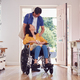 Asian Man Pushing Wife In Wheelchair At Home Back From Shopping Trip With Bag - PhotoDune Item for Sale