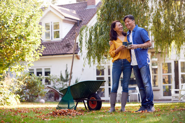 Mature Asian Couple Taking A Break With Hot Drinks Whilst Tidying Garden With Rake And Barrow - Stock Photo - Images