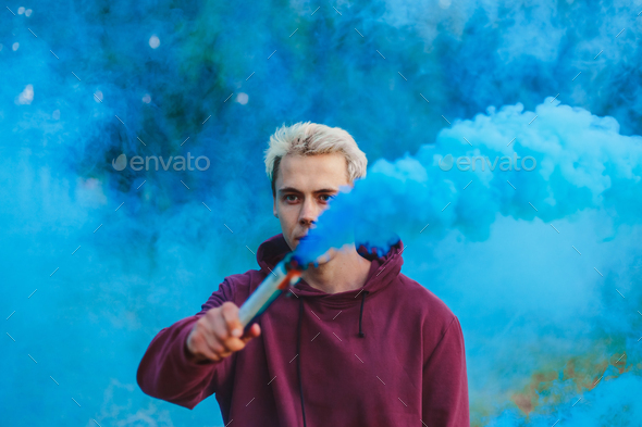 Street style man in hoodie hold hand flare with red smoke grenade bomb. - Stock Photo - Images