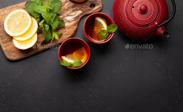 Herbal tea with mint and lemon. Tea cup and teapot - Stock Photo - Images