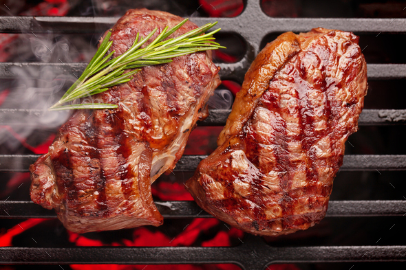 Beef steaks cooking on grill - Stock Photo - Images