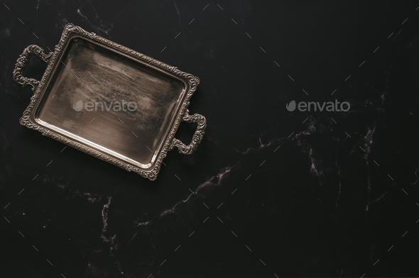 Empty antique silver tray against dark marble - Stock Photo - Images