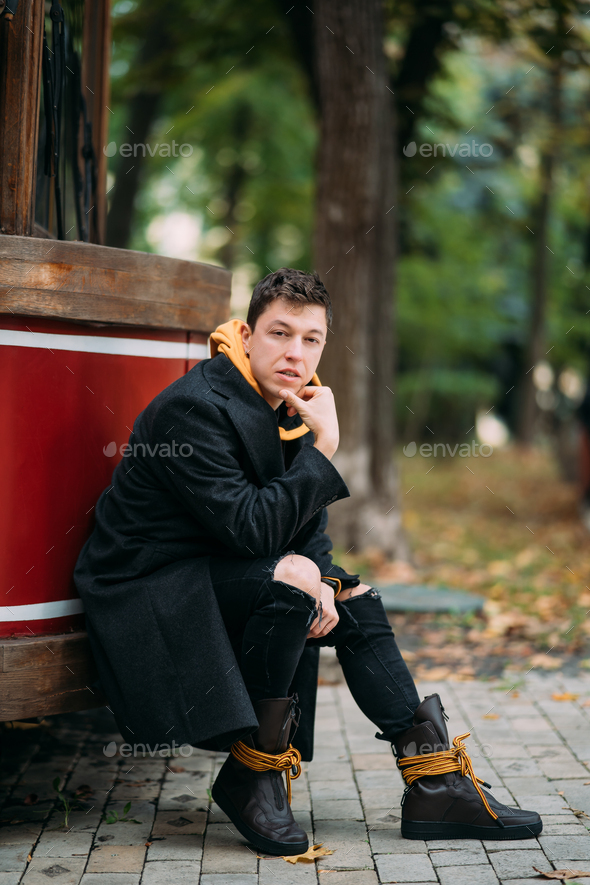 Young man in formal clothes walks in the autumn park - Stock Photo - Images