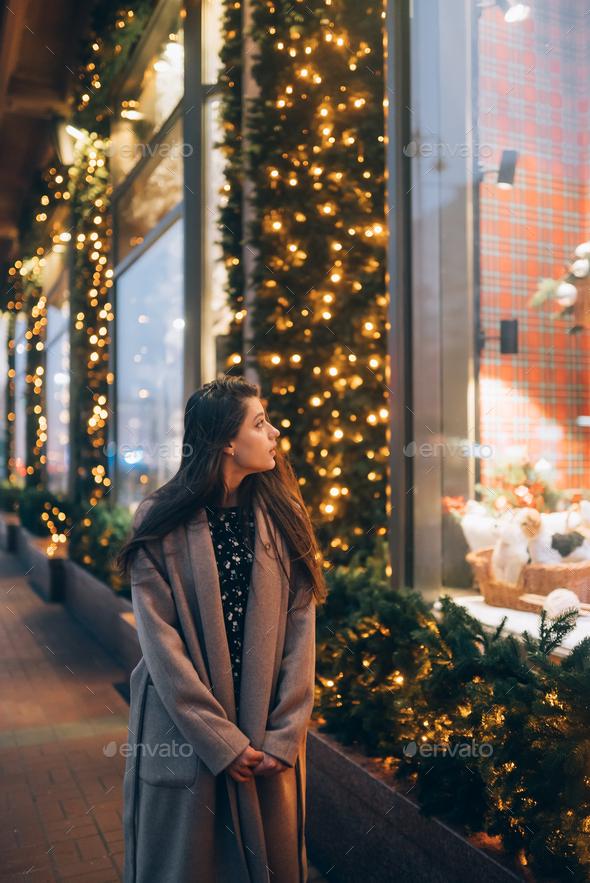 Woman by illuminated showcase on city street - Stock Photo - Images
