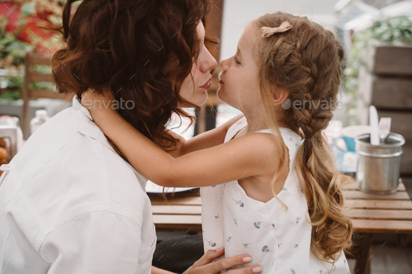 Portrait of little daughter kissing her beautiful happy mother - Stock Photo - Images