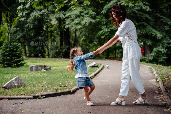 Lovely young mom and daughter in sunny day, happy family - Stock Photo - Images