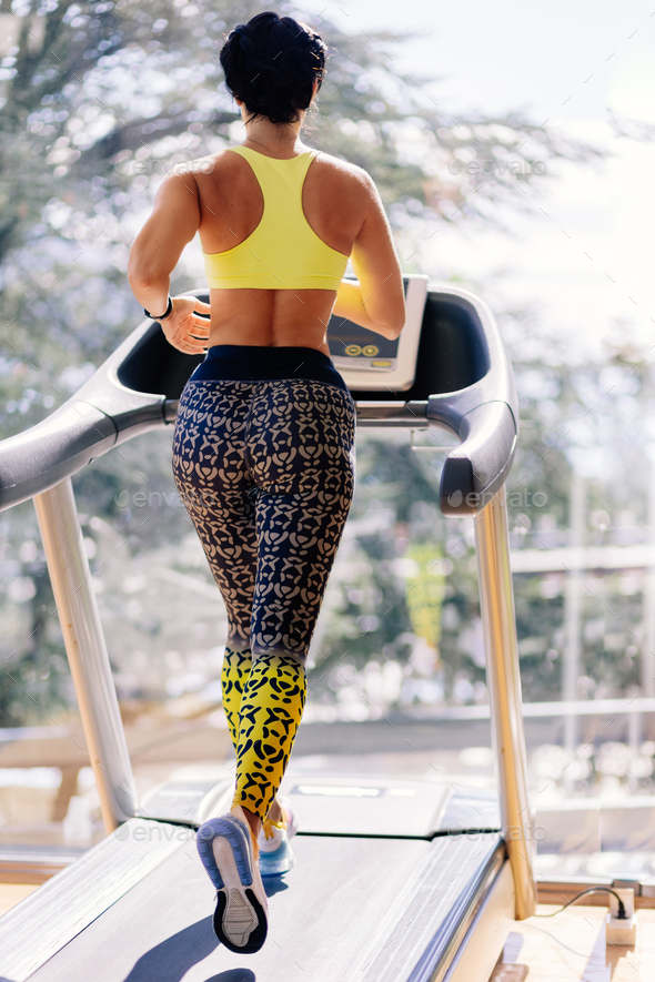 young attractive woman running on treadmill in sport gym - Stock Photo - Images