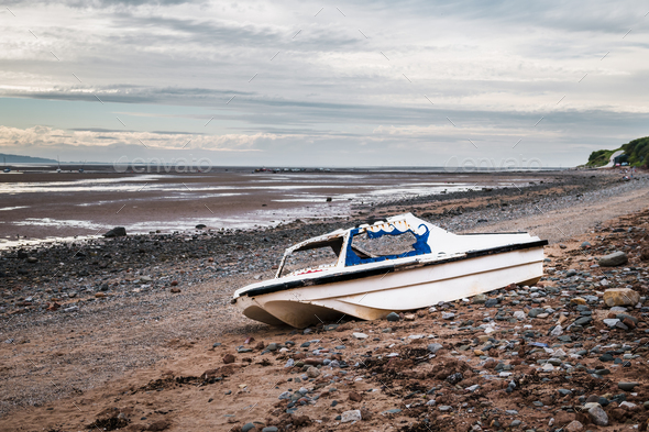 Old rusty boat on Thurstaston beach during low tide - Stock Photo - Images