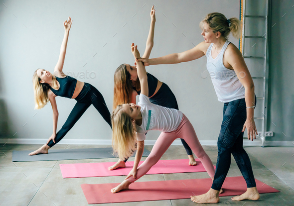 Three teenage girls doing yoga in the gym with the instructor. A healthy active sports lifestyle. - Stock Photo - Images