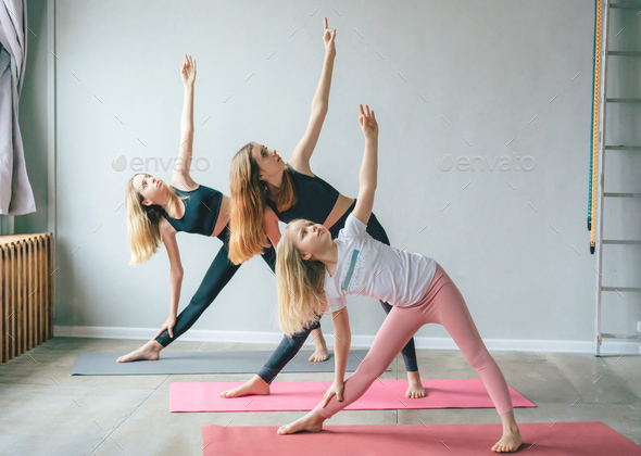 Three white teenage girls sisters in sports leggings stand in a yoga pose on the mats in the gym. - Stock Photo - Images