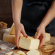 Hands holding piece of  fresh homemade cheese on a wooden board - PhotoDune Item for Sale