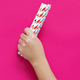 Hand with paper drinking straws on pink background close up - PhotoDune Item for Sale