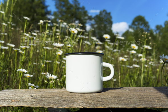 Placeit-White campfire enamel mug mockup with daisy field - Stock Photo - Images