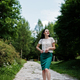Brunette girl in green skirt and white blouse posed at park. - PhotoDune Item for Sale