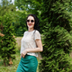 Brunette girl in green skirt and white blouse with sunglasses posed at park. - PhotoDune Item for Sale