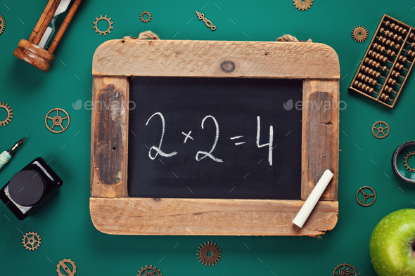 Retro school accessories with math problem on old chalkboard. Back to school concept - Stock Photo - Images