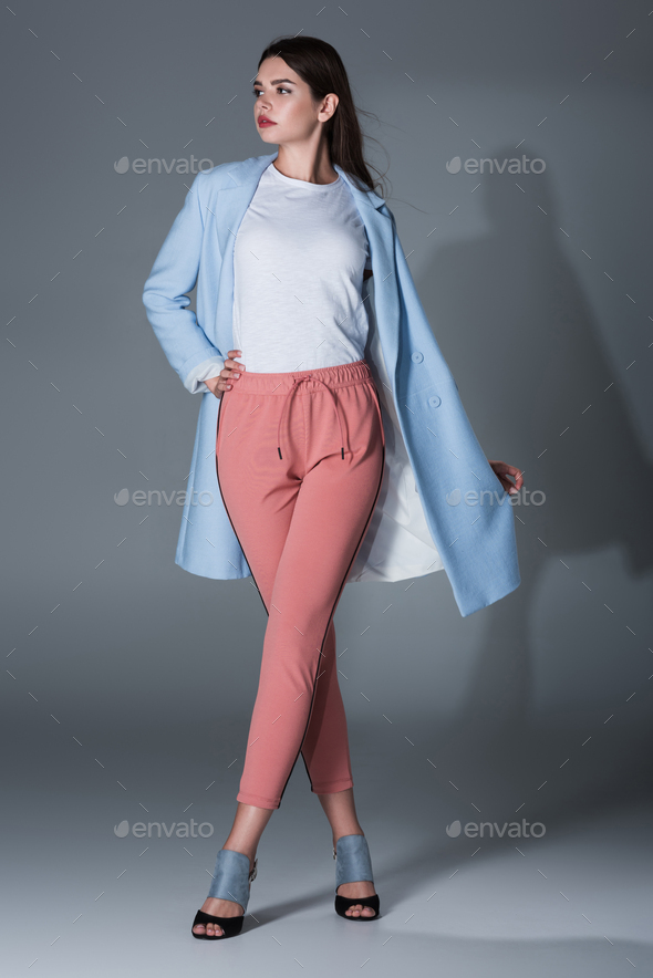 elegant model posing in blue trench coat and pink trousers, on grey - Stock Photo - Images