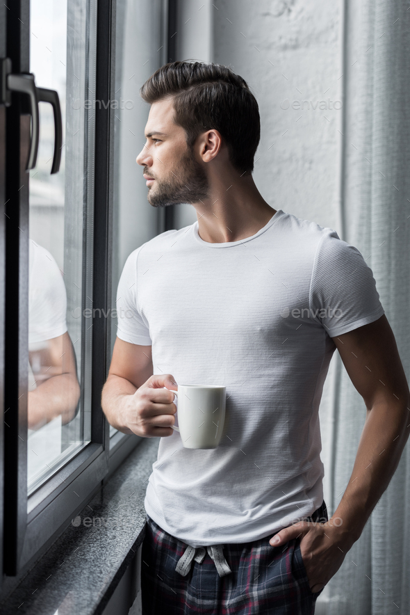 handsome man drinking coffee and looking through window - Stock Photo - Images