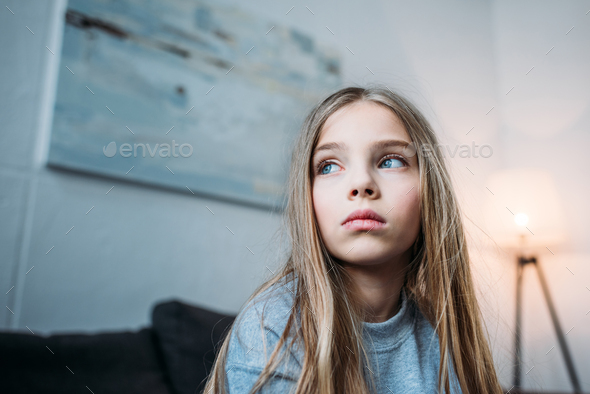 Low angle view of pensive little girl in pajamas looking away at home - Stock Photo - Images