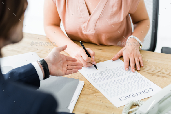 cropped view of businesspeople signing contract in office - Stock Photo - Images