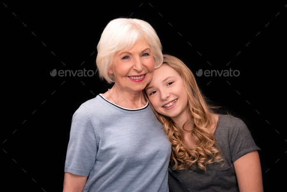 Happy grandmother and granddaughter standing together and smiling isolated on black - Stock Photo - Images