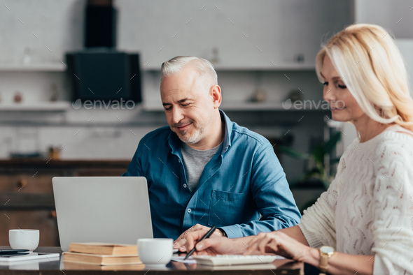 selective focus of cheerful man sitting and looking at laptop near attractive blonde wife - Stock Photo - Images