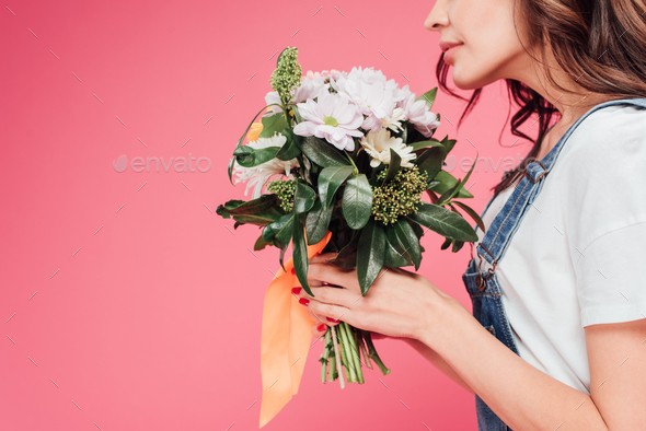 cropped view of woman holding flower bouquet isolated on pink - Stock Photo - Images