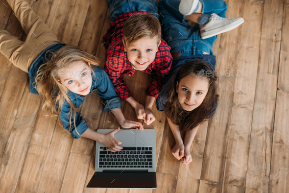 overhead view of little children using digital laptop at home - Stock Photo - Images