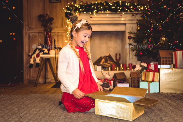 Excited girl sitting on carpet and opening christmas present - Stock Photo - Images
