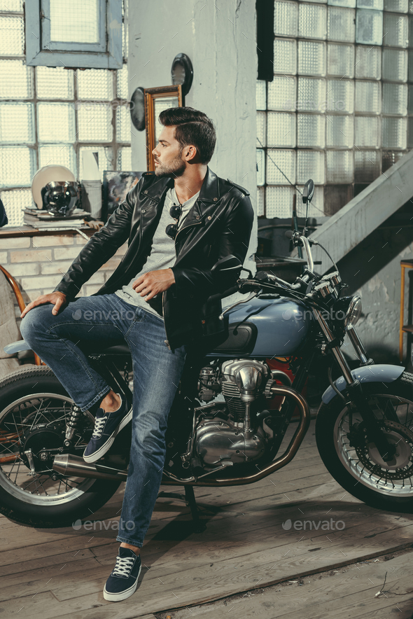 young handsome motorcyclist in black leather jacket with classic motorbike in workshop - Stock Photo - Images