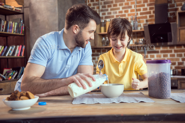 Father and son preparing chocolate corn balls with milk for breakfast - Stock Photo - Images