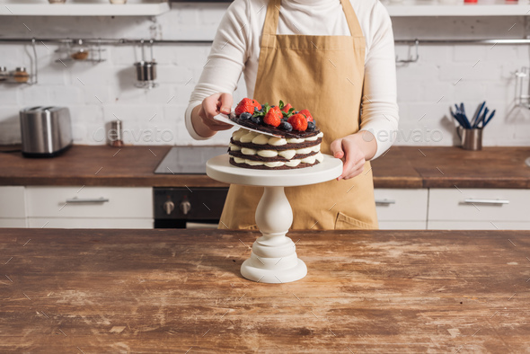 cropped shot of woman in apron preparing delicious cake with fruits - Stock Photo - Images